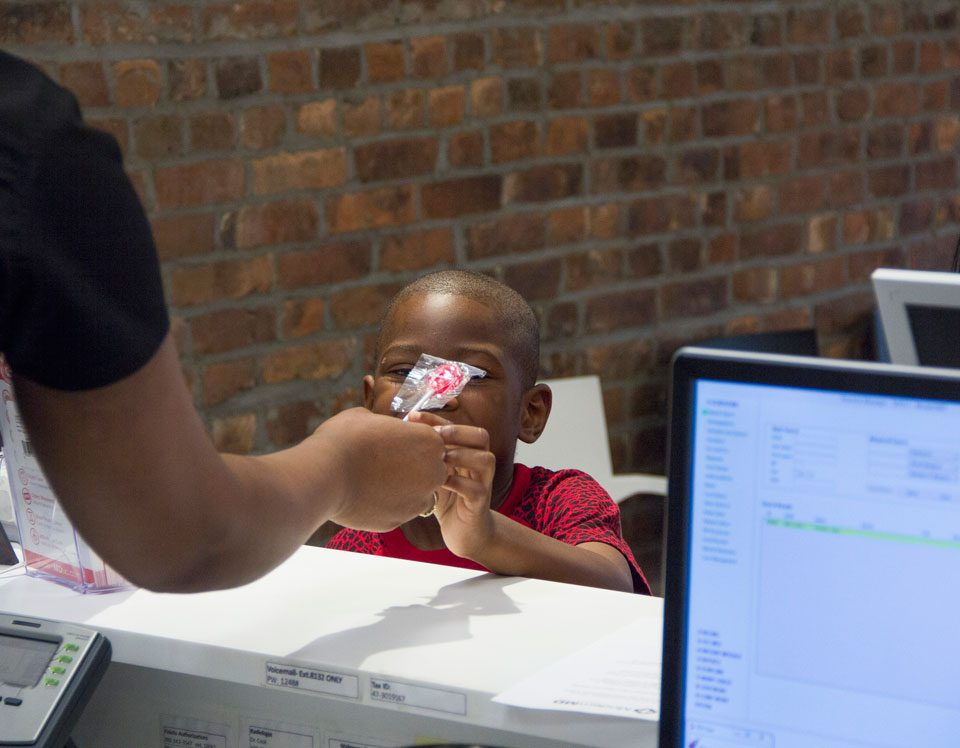 A child receiving a lollipop from the modern md staff